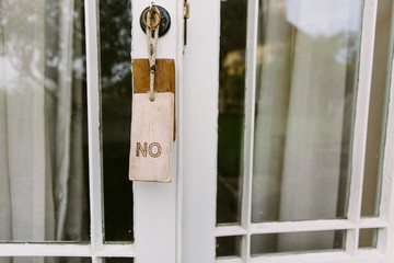 A sign saying No hanging on a door.