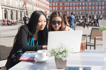 Two female Asian friends working and sitting outside a cafe In Madrid