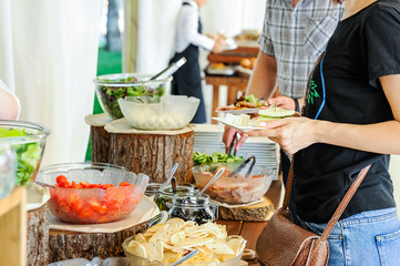 Outdoor Cuisine Culinary salad bar Catering. Group of people in all you can eat. Dining Food Celebration Party Concept. Service at business meeting, weddings. Selective focus.