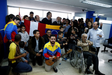 Peru's Interior Minister Basombrio poses for a picture with Venezuelan citizens who receive a temporary residence visa at the Immigration office in Lima