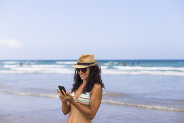 young beautiful happy woman using her mobile phone at the beach. Sea and clear blue sky background. Summer. Lifestyle