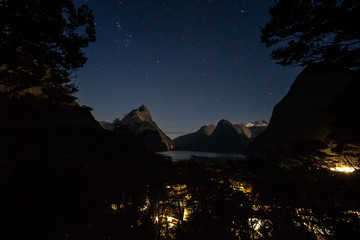 View over Milford Sound at night through the trees