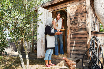 Mother and daughter gathering eggs from their backyard chicken coop