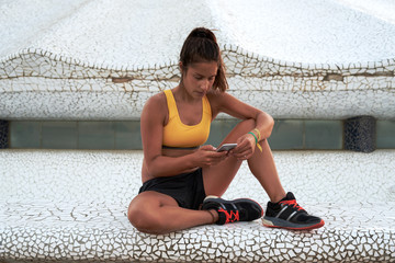 Tanned sportswoman using mobile while sitting outdoor