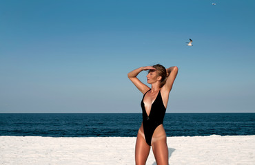 Beautiful woman in black swimsuit on the beach.