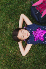 Girl day dreaming in the grass with a backpack