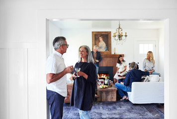 Senior couple with group of friends and family having a cocktail party in their home