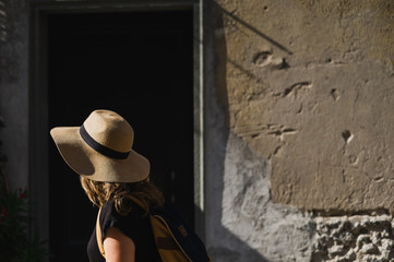 Woman walking with summer hat and sunshine
