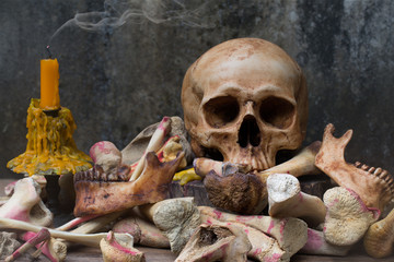 Skull with pile of bone and candle with smoke on the old wooden plate and old dirty wall in Halloween night