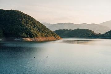 Couple kayaking on the lake in sunset