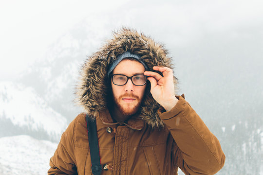 Man Outside In Snow Wearing Jacket With Furry Hood