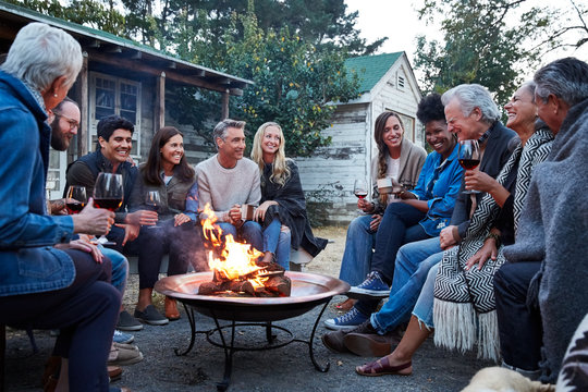 Group of friends and family relaxing around fire pit at farm