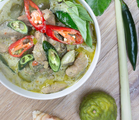 Green Chicken curry in the white bowl and fresh spice seasoning on brown wooden background (Thai food)