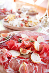 Italian antipasti and appetizers. board with slices prosciutto, salami, dried pork, salami ham with herbs.