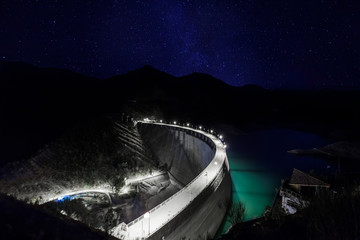 Barrage dam at night under starry sky and milky way