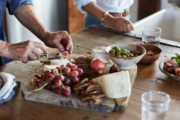 Couple making a cheese plate in the kitchen