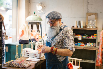 Fashionable Elderly Hipster With Grey Beard Looking at Artisan Notebook