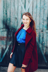 Cute long-haired girl with dental braces smiling to the camera. Wearing red coat, black skirt and blue shirt and posing outdoor
