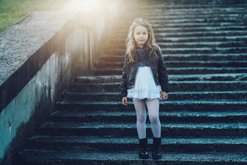 Stylish little girl in black leather jacket and white skirt posing outdoor