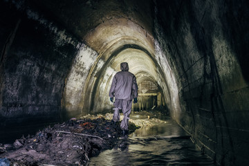 Sewer tunnel worker in chemical protective suite in underground gassy sewer tunnel