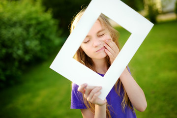 Cute cheerful little girl holding white picture frame in front of her face