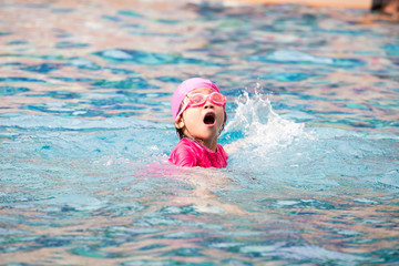 Smiling baby girl wearing swimming glasses in swimming pool.