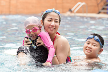 Happy family, active mother, daughter and sun having fun in a swimming pool