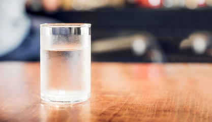 Close up Glass of cold water on wood  table in coffee shop blur background