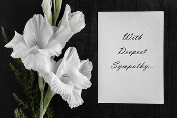 White blank condolence card with text and white gladiolus flower on the dark background.