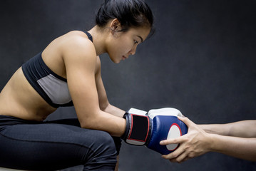 Young Asian woman boxer with blue boxing gloves concentrating with her trainer's hand in training gym, Martial arts on black background
