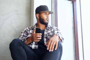 A black male sits near window and using a smartphone.