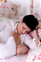 Breastfeeding baby. Young mother holding her newborn child. Mom nursing baby. Woman and new born boy in white bedroom.