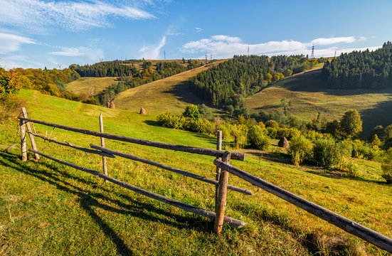 hay stacks behind the fence on rural field. lovely Carpathian hilly countryside landscape near forest in early autumn morning