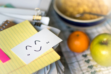 Smile Icon; Stack of Documents. Working or Studying while Eating.