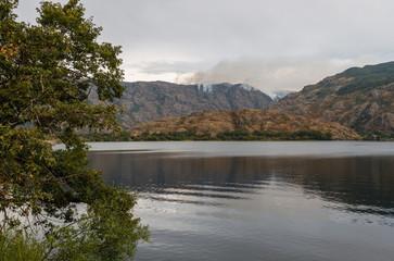Lago e incendio forestal al fondo. Parque Natural del Lago de Sanabria y alrededores, Zamora, España.