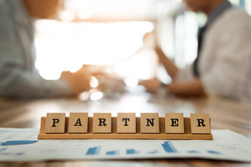 partner word on wood table with business man discuss for work during a meeting in the office, team work concept in background