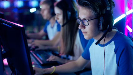 Professional Boy Gamer Plays in Video Game on a eSports Tournament/ Internet Cafe. He Wears Glasses and Headphones with Microphone. Other Girls and Boys Players Playing in Background.