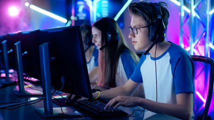 Team of Professional Cybersport Gamers Playing Video Games on a Cyber Games Tournament. Girls and Boys Have Headphones On, Arena is Lit with Neon Lights.