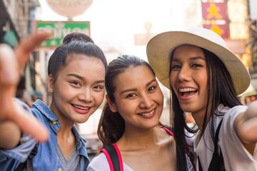 Three asian girlfriends taking selfies in Chinatown, Bangkok.