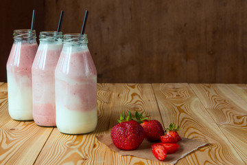 Smoothie with strawberry in bottles on wooden table