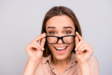 Close up of an amazed brunette young woman in beige formal shirt and glasses, holding them, she is shocked, extremely happy, with wide open eyes, on pure light grey background