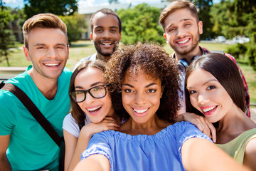 Selfie mania! Six international students with beaming smiles are posing for selfie shot, african cute lady is making, outside school building. Gathered, cheerful, smart and successful youth