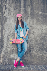 Youth culture. Young attractive hipster girl stands with skate board on concrete wall`s background, in denim outfit, pink hat and shoes, holds a long board