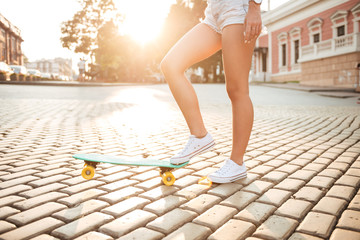 Cropped picture of young woman with skateboard