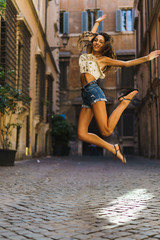 Fit girl jumping at street