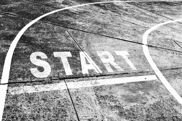 Black and white conceptual start line message on the grunge textured road.
