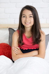 Portrait of a beautiful happy smiling girl rest on the bed