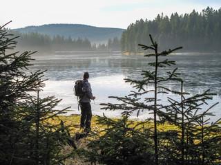 Deutschland, Niedersachsen, Sankt Andreasberg, Mann vor überfrorenem See zwischen Nadelbäumen im Harz bei Sankt Andreasberg