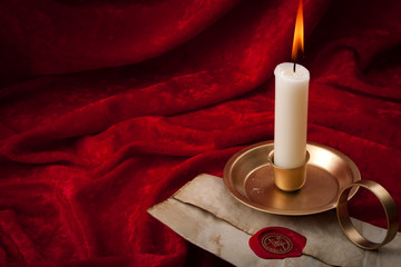 Masonic secrecy concept with a lit candle on a letter made of old vintage paper with red wax seal stamp and the freemason emblem against a scarlet color velvet background with copy space