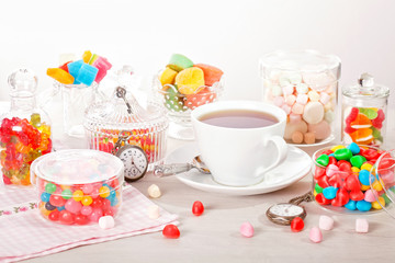 Cup of tea with assorted colorful candies for kid's birthday